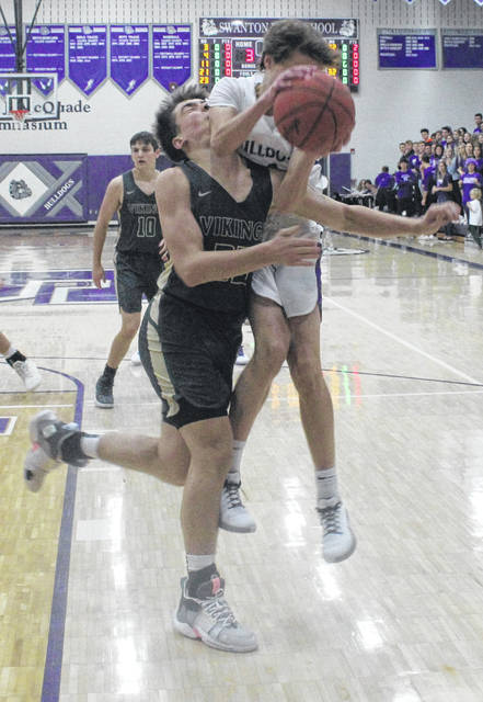 Trent Weigel of Swanton pulls down a rebound over Ethan Loeffler of Evergreen on Friday.