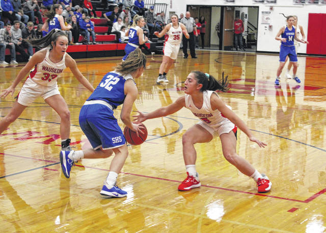 Autumn Pelok of Wauseon, right, reaches in against Stryker's Sage Woolace (32) looking to force a steal while teammate Sam Aeschliman, left, offers assistance. The Indians, behind a strong defensive effort, defeated the Panthers 50-15 in a non-league game Thursday.
