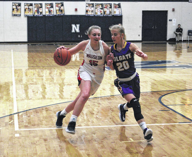 Marisa Seiler of Wauseon drives on Raena Willett of Holgate (20) during Saturday's consolation game of the Northwest Signal Holiday Classic. After falling to Napoleon 50-36 on Thursday, the Indians bounced back with a 49-29 win over the Tigers.