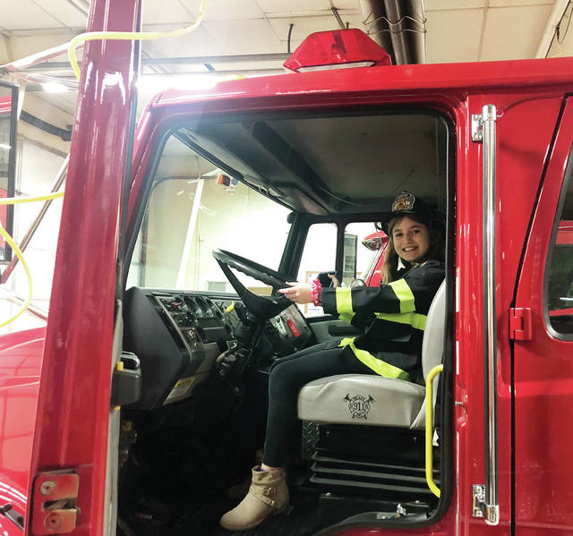 Aida Alig of Delta sits high in the driver's seat of a Delta Community Fire Department engine.