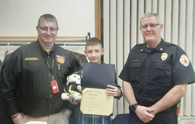 Fire Safety Educator Dale Schulte, left, presented 13-year-old Jayden Griggs with a Smoke D.O.G. award after he alerted family members to a fire that destroyed their rural Delta home. Also pictured is Delta Police Chief Scott Smith, who nominated Jayden for the honor.