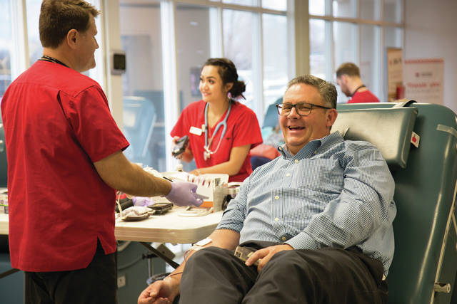 Donor Thomas Brown finishes giving whole blood with American Red Cross staff member Alex White.