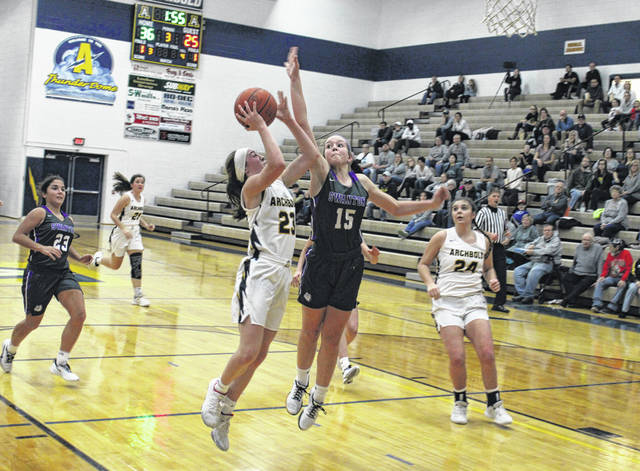 Kylie Sauder of Archbold draws contact from Swanton's Frankie Nelson (15) during Friday night's NWOAL opener. The Blue Streaks held on for a 48-41 win over the Bulldogs.