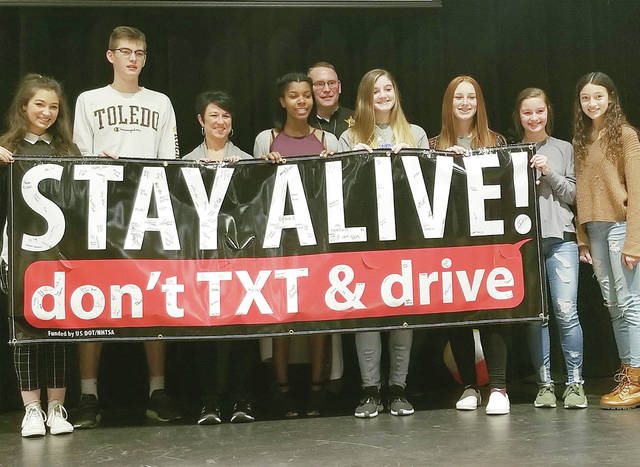 "Pettisville FCCLA chapter members and event presenters posed with a ""Stay Alive - don't text and drive"" banner. Pictured are, from left, Rylee Beltz, Cayden Jacoby, FCHD Educator Rachel Kinsman, Xavia Borden, Fulton County Clerk of Courts Tracy Zuver, Elisabeth Rochefort, Taylor Boger, Hollyn Klopfenstein, and Cassidy Miller"