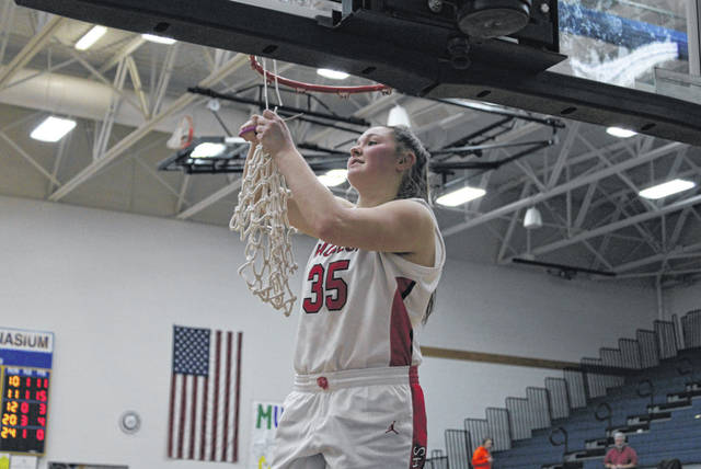 Wauseon senior Sydney Zirkle finishes off the cutting of the net after the Indians' 54-49 win over Bryan Saturday to win a sectional title. It was their second straight sectional championship.