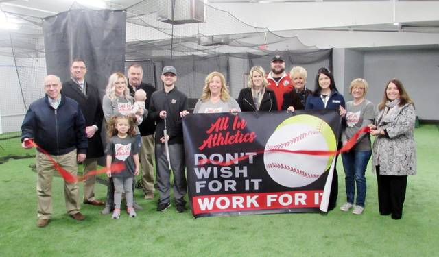All In Athletics co-owner Dylan Leu did the honors during a ribbon cutting ceremony at the new business, held Jan. 31. He and co-owner Stacie Radabaugh, center, offer cage rentals, instruction, pitching lessons, and team rentals at the athletic facility at 229 N. Fulton St. in Wauseon. Hours are M-F, 4-9 p.m.; Saturday, 10 a.m.-4 p.m.; Sunday, noon-5 p.m. For information, call 419-822-6419. Also pictured are family members, Wauseon Mayor Kathy Huner, far right, and Chamber of Commerce members.