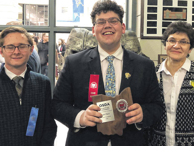 Noah Harman, center, poses following a previous win with WHS speech coach Dolores Muller, right, and assistant coach Justin Mourguet.