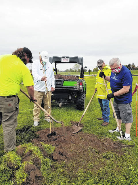 From left, a City of Wauseon employee and city Tree Commission members Jim Spiess, Larry Frey, and Rick Frey planted a Kentucky Coffee tree at Wauseon Primary School in honor of Arbor Day, which was held April 24. That tree and others the members planted for the occasion were donated by Woody Warehouse of Lizton, Ind.