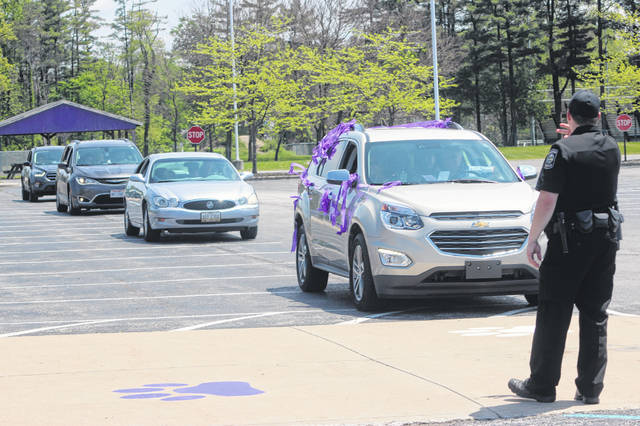 Swanton police officer Lee Kusz directs vehicles during Swanton's drive thru graduation ceremony on May 24.