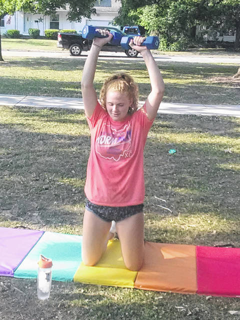 Grace Ellis limbers up with some five-pound weights before a Wednesday training session at Wauseon's city pool with the Bowling Green State University Falcons Swimming and Diving Team.
