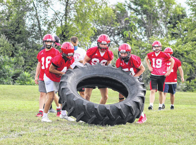 Wauseon football players work on their endurance by flipping a tractor tire across the practice field during Monday night's practice.