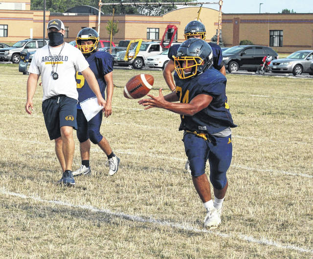 Archbold running back Noah Gomez takes a pitch as head coach David Dominique, left, looks on during practice Monday night. The Blue Streaks, with a bulk of their offense returning, hope to repeat as NWOAL champs this season.