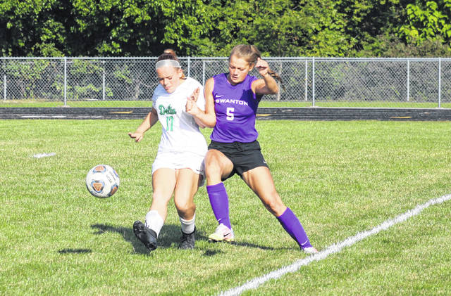 Kayla Kunar of Delta, left, kicks the ball to the sideline as Jayden Hendricks of Swanton tries to get to it. The Bulldogs pulled out a win over the Panthers with a pair of second half goals.