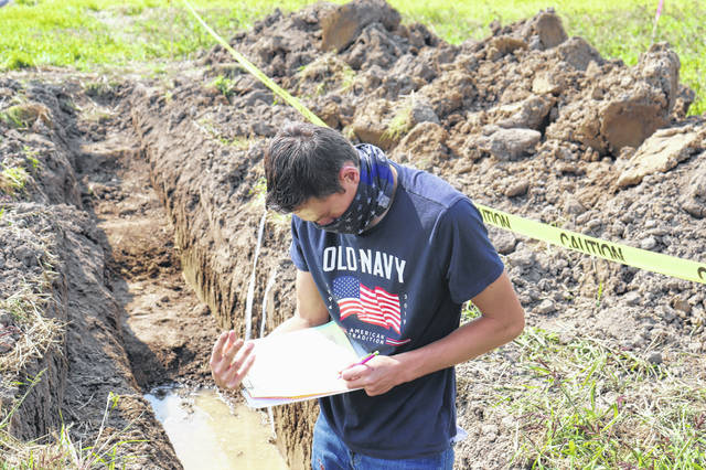 Junior Carson Bennett fills out his judging card in the pit after carefully examining the soil.