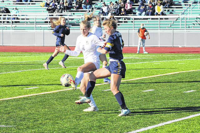 Leah McQuade of Archbold, left, tries to gain control of a ball as Emilee Horstman of Ottawa-Glandorf guards her closely during Saturday's district final. The Blue Streaks scored with just over two minutes left in overtime to earn a 2-1 win over the Titans and advance to the Division III regional semifinal.