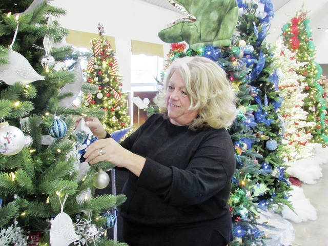 Kathy Shaw, CEO/director of Triangular Processing Inc., adjusts the decorations on one of the trees auctioned during the countywide inaugural Festival of Trees event held last year.