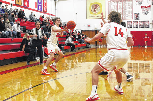 Connar Penrod of Wauseon dishes to Kolton DeGroff (14) during the NWOAL opener with Bryan Thursday. Despite trailing by double digits in the second half, the Indians overcame that deficit in the fourth quarter to earn a 38-35 win.