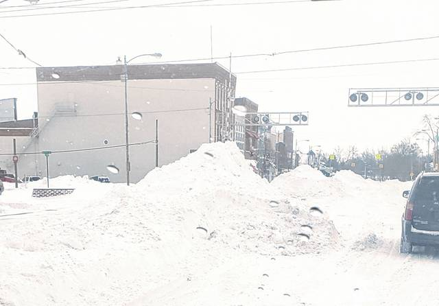 Piles of snow line Fulton Street in Wauseon Tuesday following the season's biggest winter storm. A Level 3 Snow Emergency was issued and businesses and schools closed.