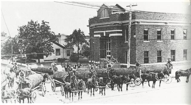 Eleven drivers and teams stopped at the corner of N. Defiance and Holland streets in Archbold on their way to the Gotshall Brothers Mill on Depot Street. Behind them is the uncompleted township hall, now the Archbold Municipal Building. You can also see the high-tension electrical lines used by the Toledo & Indiana Railway interurban trolley lines. The picture was taken in 1911 by C.W. Waldvogel.