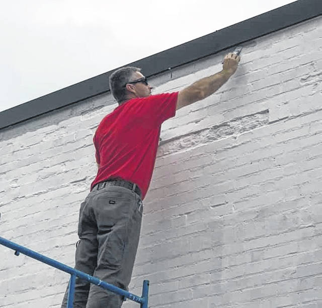 Wauseon High School art teacher Mike Colon, a leader of the project, paints a top portion of the mural on the side of the CenturyLink building located at 146 N. Fulton St. in Wauseon. The project should be finished by the end of summer.