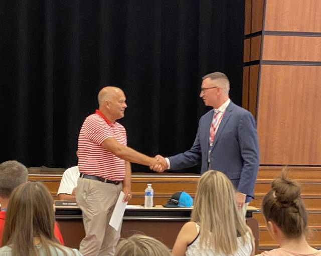 Matt Hutchinson, left, Wauseon's district athletic director, was honored by Superintendent Troy Armstrong as the 2020-21 recipient of the Ohio Interscholastic Athletic Association Meritorious Service Award. The school board honored Board of Education Vice President and former football coach Larry Fruth by designating the district's football field Larry Fruth Stadium at Harmon Field.