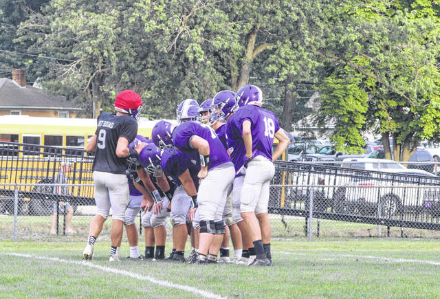 The Swanton football team huddles during a scrimmage with Ayersville on Thursday.