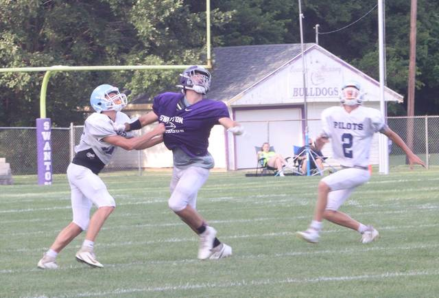 Lathan Pawlowicz of Swanton looks for a pass between two Pilot defenders last Thursday.