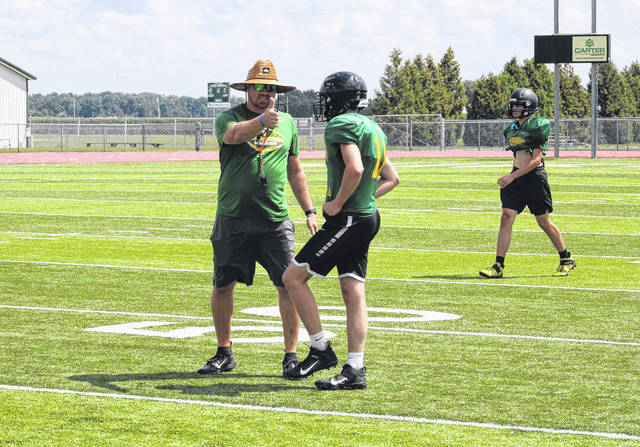 Evergreen head football coach Aaron Schmidt gives instructions to one of his defensive backs during the defensive portion of Tuesday's practice.