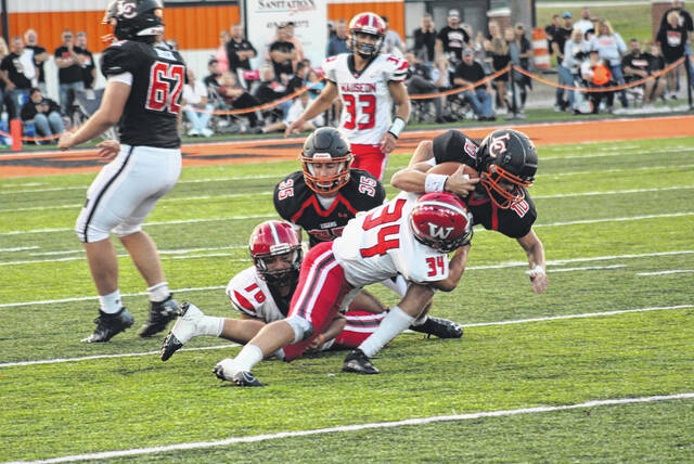 Wauseon's Zaidan Kessler makes a tackle on Liberty Center quarterback Zane Zeiter in the first quarter of Friday night's game. The Tigers would defeat the Indians in overtime, 34-28.