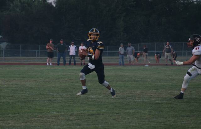 Archbold quarterback DJ Newman rolls to his right and looks for a receiver last Friday against Liberty Center. The Blue Streaks were rated first in Division VI, Region 22 in the latest OHSAA computer ratings.