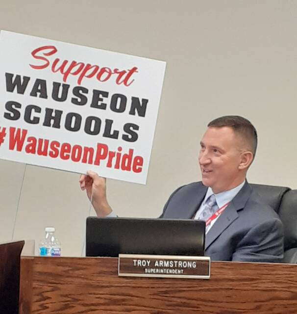 Superintendent Troy Armstrong displayed a lawn sign promoting the proposed 2% earned income levy during a discussion Monday at the Wauseon Board of Education meeting.