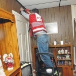 Sidney firefighters and the Red Cross install smoke detectors