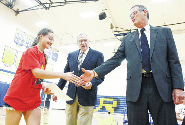 Carly Supinger, far left, of Russia, daughter of Mike and Shirley Supinger, shakes hands with Russia Mayor Terry Daugherty, far right, after receiving her DARE diploma from Shelby County Sheriff John Lenhart, center.