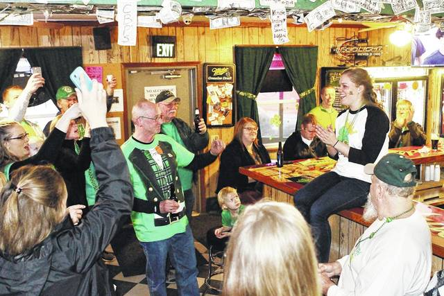 Katie Niekamp, right, on bar, of McCartyville, is toasted as the St. Patrick's Day queen of McCartyville inside Patrick's Pub and Grill Friday, March 17. Reading the toast was Randy Otting, left, of Minster. Niekamp is the daughter of Juanita and Louis Niekamp