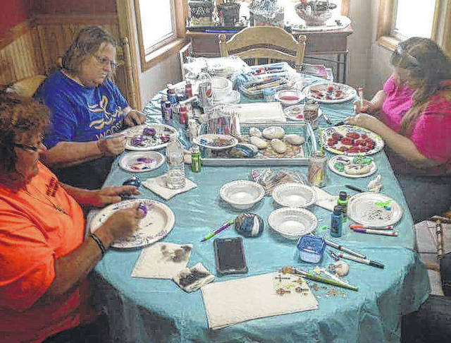 West Central Ohio Rock Administrator Debbie Fields, left to right, co-founder Sharon Fiely and co-founder Kristy Miller paint a batch of kindness rocks at Fiely's home. The group's purpose is to spread kindness through out the community.