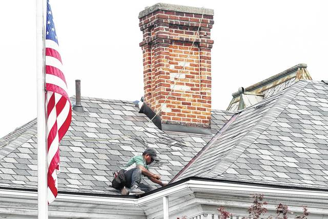 A&E Home Services employee Bico Morales, of Dayton, finishes up reshingling the roof of the Ross Historical Center Tuesday, Sept. 12. A&E Home Services employees removed four layers of old shingles during the project which started Saturday, Sept. 9. Next peeling paint will be scraped off and the building will be painted.