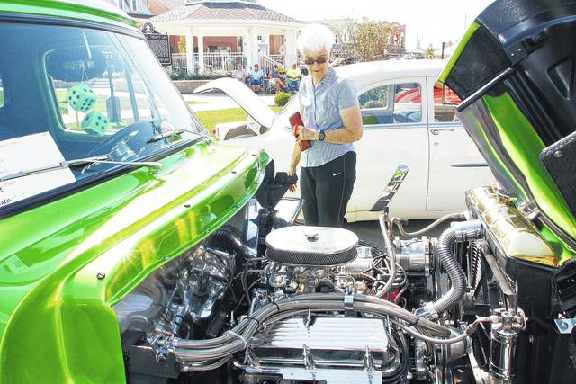 Shirley Larger, of Fort Loramie, looks at the engine of a 1953 Ford F-100 owned by Phil Battels that was on display at the Fort Loramie German Heritage Days car show Saturday, Sept. 23.