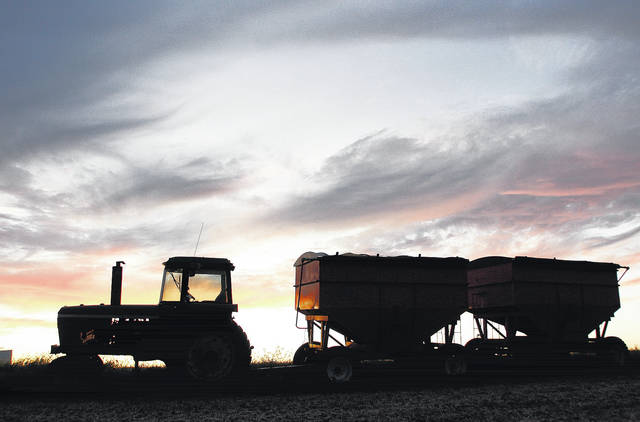 A tractor sits in a field along Russell Road with two loads of freshly harvested soybeans attached to it at sunset Monday, Sept. 25.