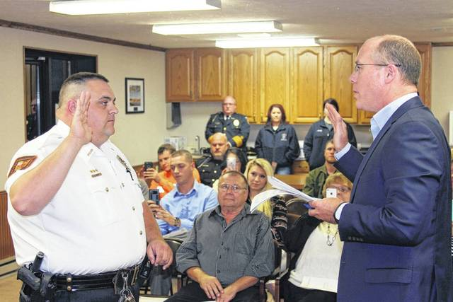 """As friends and family watch, Charles A. """"Chuck"""" Wirick, left, is sworn in to serve as the new police chief for the village of Jackson Center. Reading the oath of office is Village Solicitor Mike Burton."""