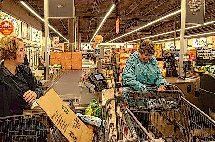 Bryan Reynolds | The Lima News Aldi Cashier Crystal Huber, on loan from Lima, cashing out Kathy Dirksen, of Wapakoneta, during the grand re-opening of the Wapakoneta Aldi store after five weeks of being closed for remodelling.