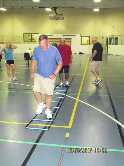Tom Clark, front, and Mike Herbert run through a ladder during an exercise in the Delay the Disease class at the Sidney-Shelby County YMCA.