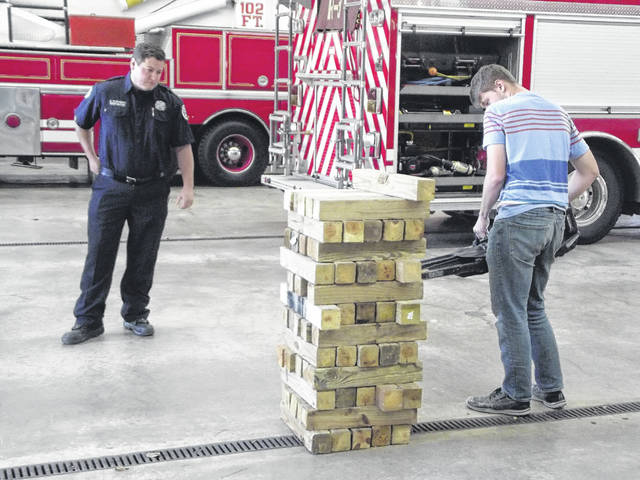 """Sidney Firefighter Chance Guisinger watches as Riverside High School senior Evan Kauffman uses battery-operated """"jaws of life"""" to remove a block of wood from a large Jenga display Tuesday at the fire department. The demonstration shows how the firefighters use the equipment to free people trapped in a vehicle. The new equipment is battery operated thus eliminating the cords which provided power for older jaws of life."""