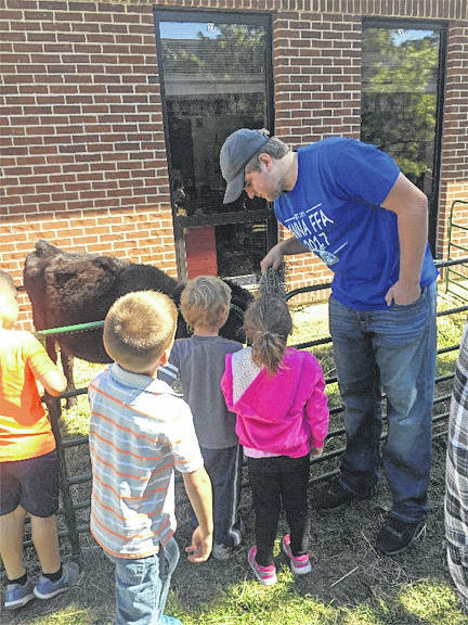 Anna High School FFA member Cole Albers helps children who attend the Shelby Hills Childhood Center feed the animals at the petting zoo during the center's fall fun day in Sidney, recently.