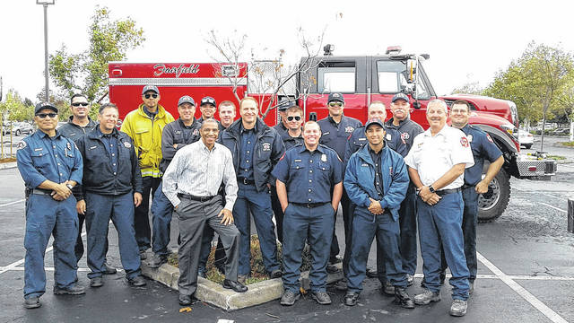 """Former Sidney resident Gregory Stockton-Bolden, of Pleasanton, Calif., front row center in checked shirt, poses in Fairfield, Calif., with Northern California firefighters from the Napa Valley area that was recently devastated by wildfires. Bolden, a former public affairs producer for KNTV/NBC in San Jose, is the son of Bradley Bolden, of Fairfield, Calif., and Sylvia Hudson, of Sidney. Drizzling rains in the Napa Valley area have given the firefighters a much-needed break from tragic fires that have destroyed thousands of acres in Northern California and claimed more than 42 lives. Bolden said, """"It was an honor to stand beside a group of men who are willing to risk their own lives for the sake of others and the preservation of wildlife."""""""