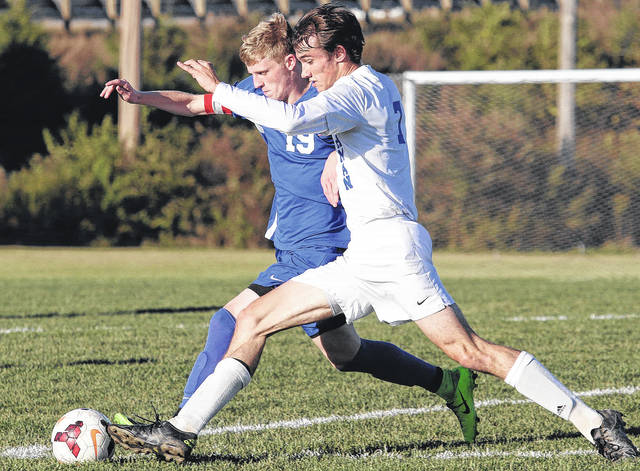 Lehman's Conor O'Leary, front, races Greeneview's Quentin Conley for the ball at Lehman on Tuesday. The Cavaliers won 2-0 to advance to a second-round game on Saturday at Troy Christian.