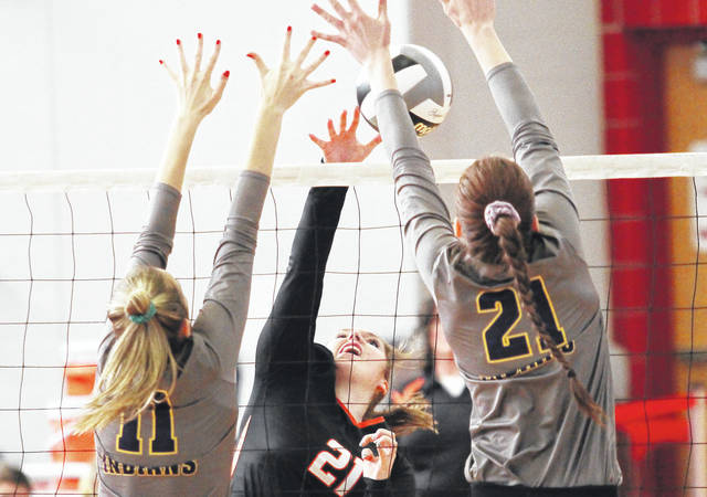 Jackson Center's Riley Jackson (center) spikes the ball at Mechanicsburg's Taylor Ayers (left) and Emma Dunham (right) on Wednesday in a Division I sectional opener at Troy.