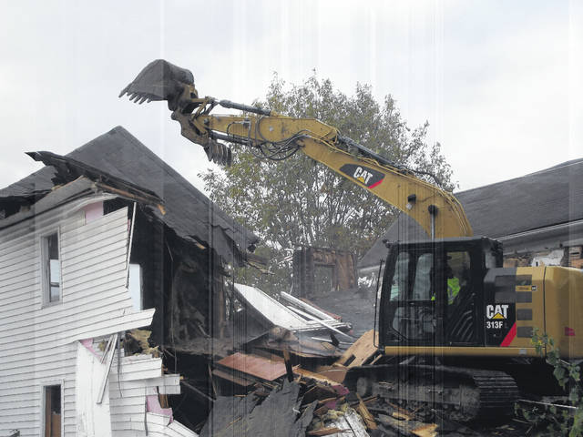 The first of six houses in the 300 block of East Court Street in Sidney is being demolished Tuesday morning. The houses — 342 to 352 E. Court St. — were purchased by the Shelby County Land Reutilization Corp. (land bank) and will be torn down and the land refurbished into a new life.
