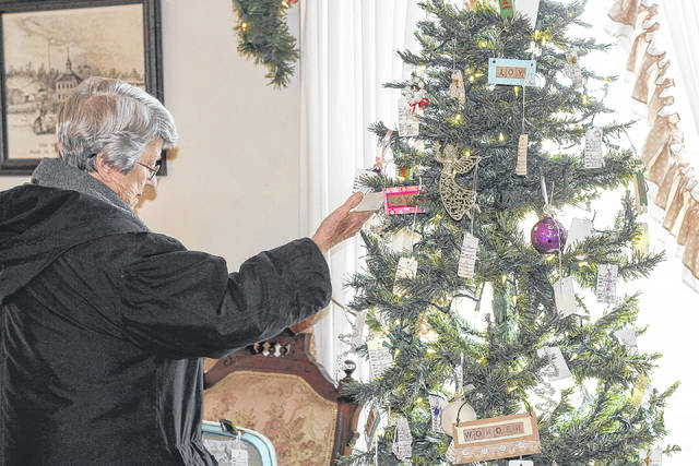Carmen Eberhardt, of Sidney, selects an ornament from a decorated tree at the Angels in the Attic craft show in the Ross Historical Center in Sidney, Friday, Nov. 10.