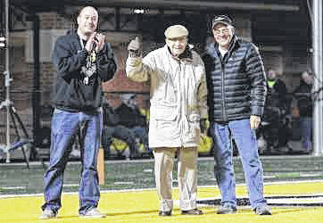 Sidney Athletic Dirctor Mitch Hoying, left, introduces Norris Cromes, 97, center, during the Sidney vs Belmont football game Friday, Nov. 3. Cromes was the quarterback of the 1937 Yellow Jacket football team that won the Miami Valley league with a record of 9-0-1. This year marks the 80th anniversary of the school's first football league title. Cromes is also a World War II veteran. At right is Norris's son, Gary Cromes.