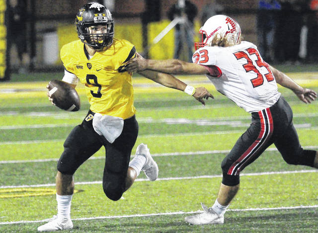 Sidney's Andre Gordon (left) runs from Tippecanoe's Mason Doll (right) during a Greater Western Ohio Conference game on Oct. 5 at Sidney Memorial Stadium. The Yellow Jackets are in the playoffs for the first time since 1989.